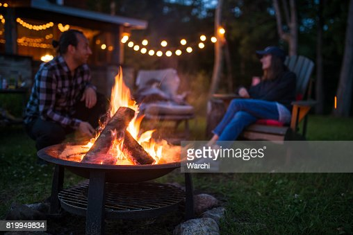 Young family is warming near campfire late evening at a beatiful canadian chalet