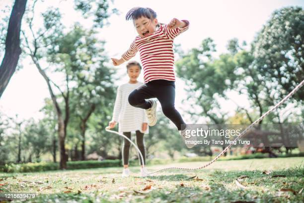 young family jumping rope joyfully on the lawn - playing stock-fotos und bilder