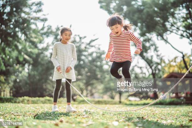 young family jumping rope joyfully on the lawn - wellness stock pictures, royalty-free photos & images