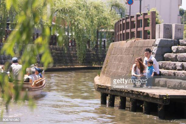 Young family looking at tour boat on river