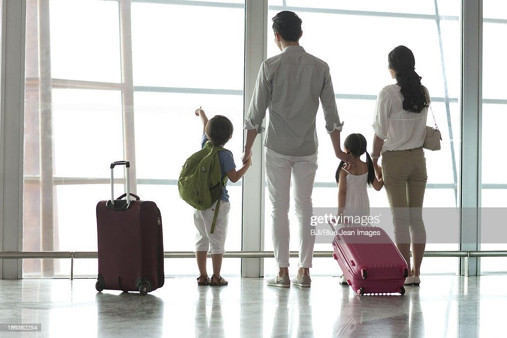 Young family looking at view at the airport : Stock Photo