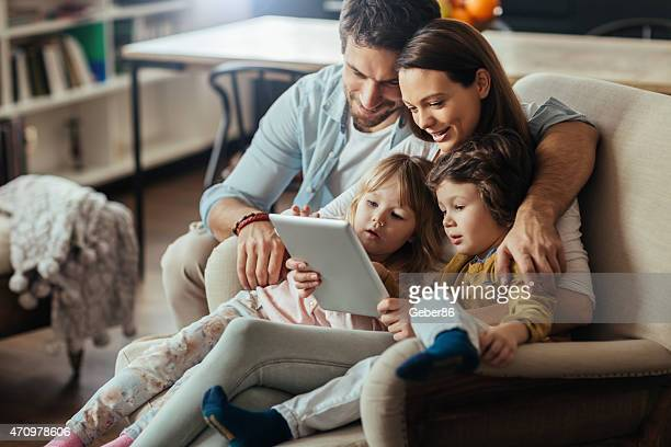 Young family looking digital tablet