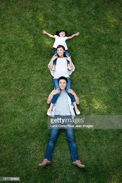 young family lying down and playing on the grass - down blouse stock pictures, royalty-free photos & images