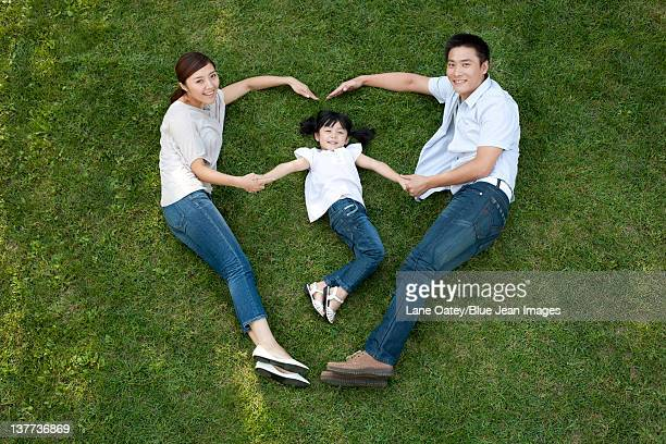 young family lying down and pretending to run on the grass - down blouse stock pictures, royalty-free photos & images