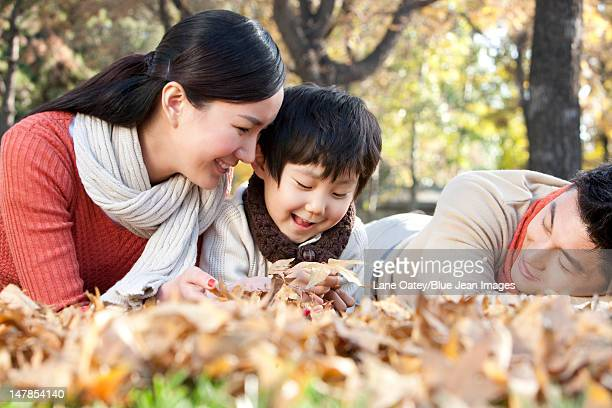 Young family lying on the grass surrounded by Autumn leaves