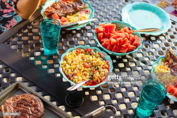 young family millennial parents with female child eating at patio dining table cookout bbq photo series - eyecrave  stock pictures, royalty-free photos & images
