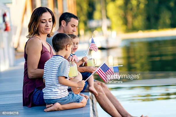 Young family of four drinking lemonade by the river