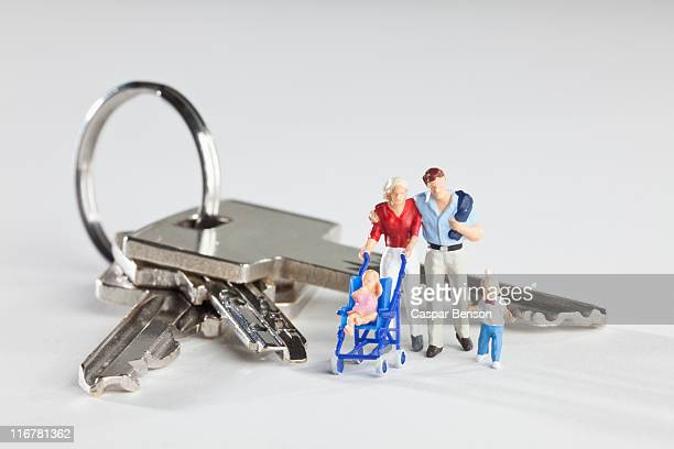 a young family of miniature figurines standing next to house keys on a key ring - human representation stock pictures, royalty-free photos & images