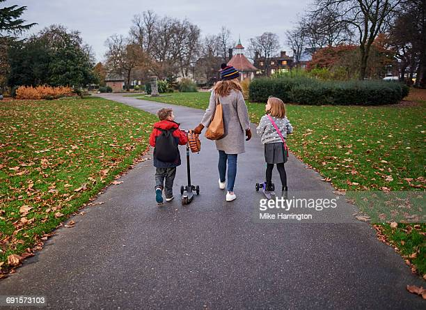 Young family on school run on autumn afternoon