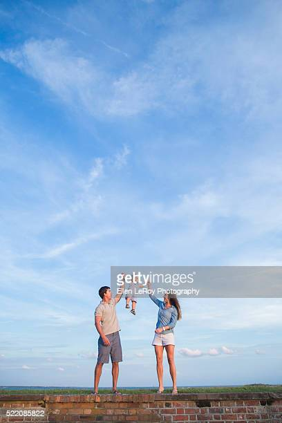 young family on wall lifting one-year-old child into the air - atlantic beach north carolina stock pictures, royalty-free photos & images