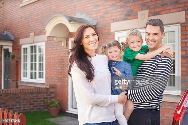 young family outside their home