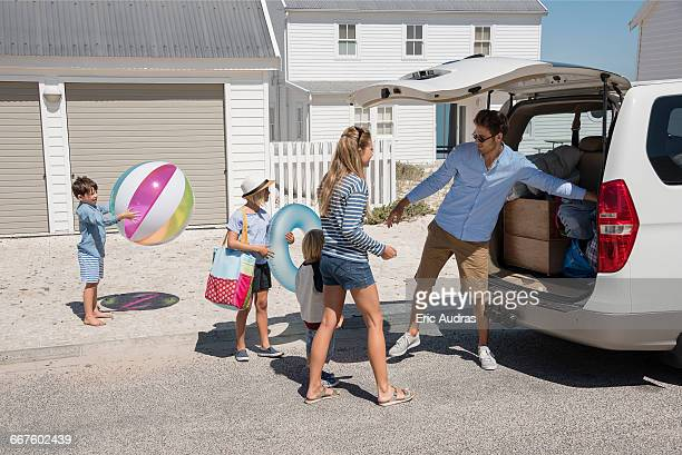 Young family packing car with beach gears for vacation
