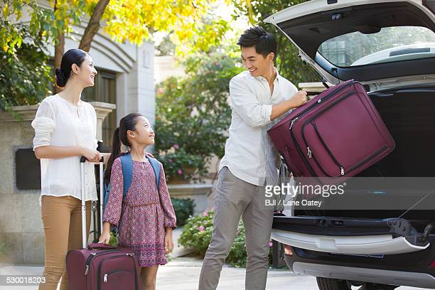 Young family packing for car trip