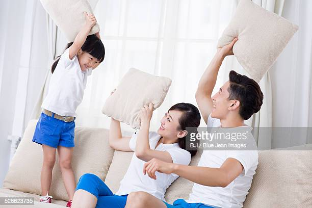 Young family pillow fighting on the sofa