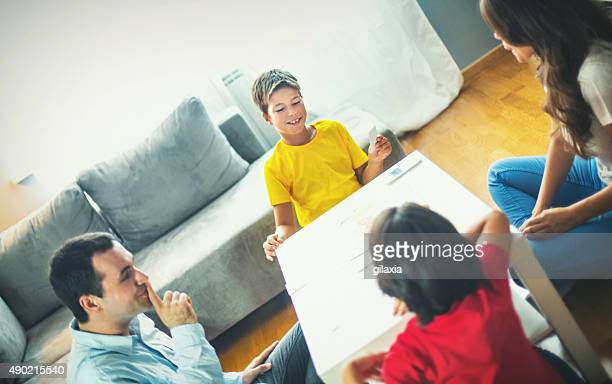 Young family playing board game at home.