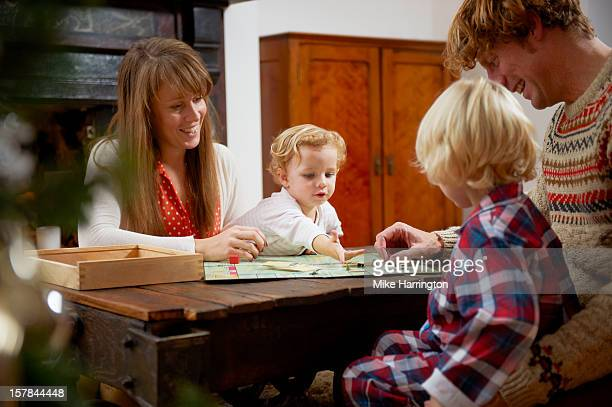 Young family playing board game on table in lounge
