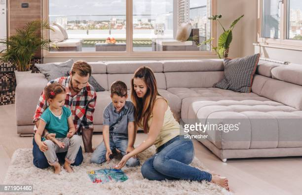 Young family playing cross and section game on a carpet at their penthouse.