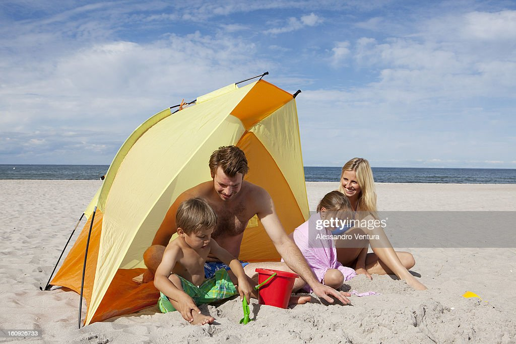 young family playing in front of tent on beach  Stock Photo & Young Family Playing In Front Of Tent On Beach Stock Photo | Getty ...