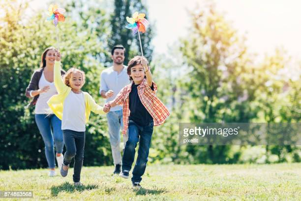 young family playing in the park - gras stock pictures, royalty-free photos & images