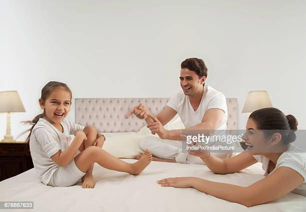 Young family playing on bed with their daughter