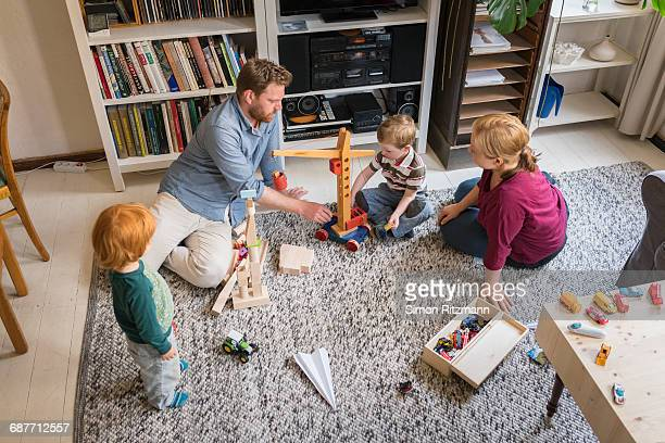 Young family playing together with wooden toys