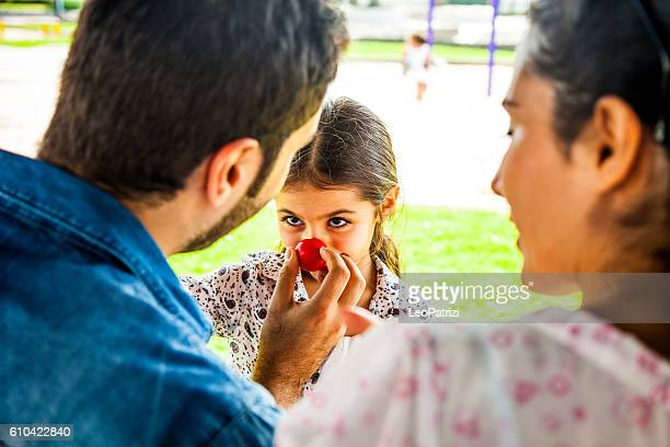 young family playing with a red clown nose - clown's nose stock photos and pictures