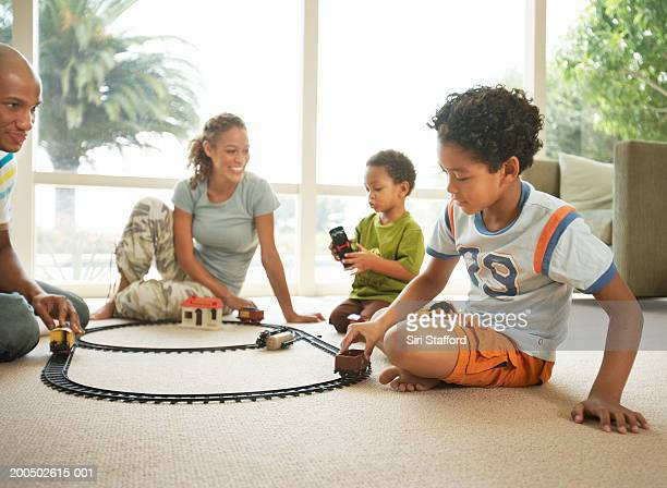 Young family playing with toy train set in living room