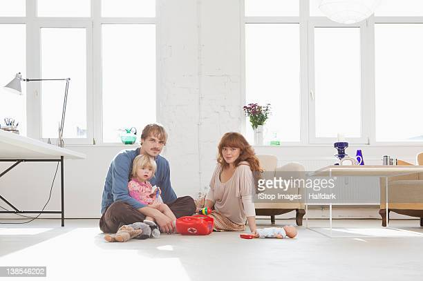A young family playing with toys on the living room floor