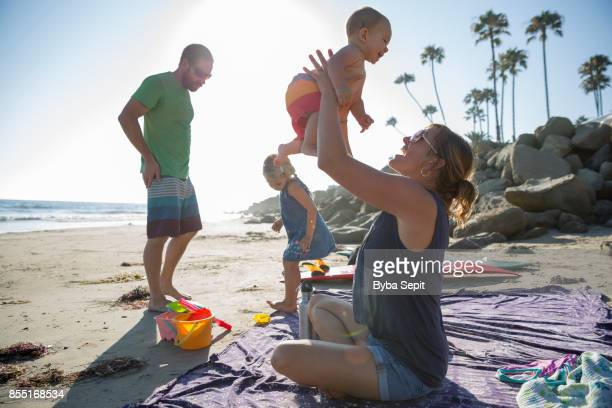 Young family plays on the beach.