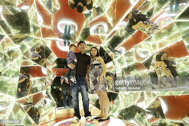 A young family pose for a photo inside a 3m tall walkin kaleidoscope on Orchard Road on November 17 2012 in Singapore Every year the famous shopping...
