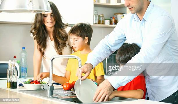 Young family preparing food in kitchen.