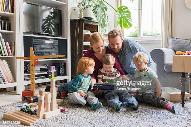 Young family reading storybook together at home