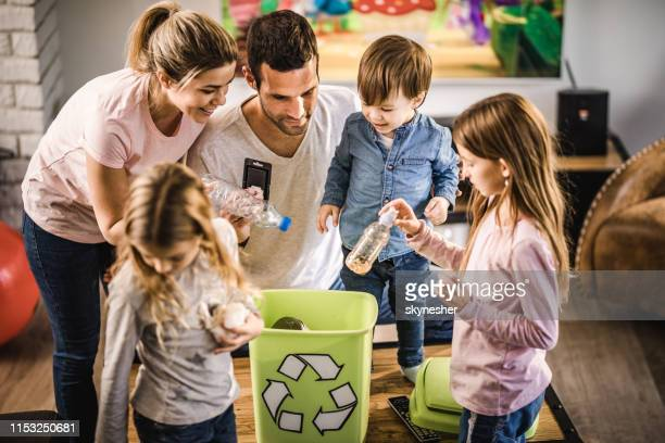 young family recycling garbage in a recycling bin at home. - reciclagem imagens e fotografias de stock
