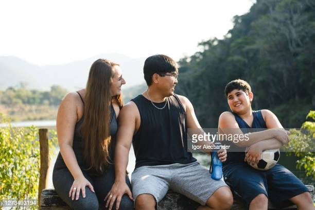 young family relaxing in nature park - sentar se imagens e fotografias de stock