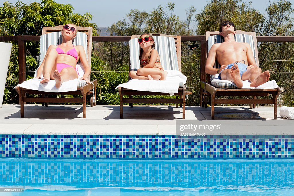 Young family relaxing on sun loungers by pool : Stock Photo