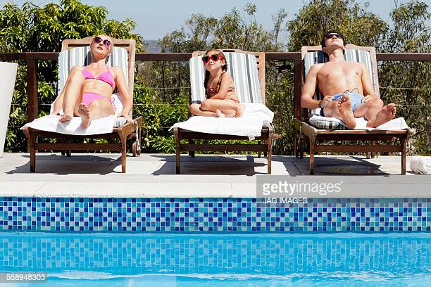young family relaxing on sun loungers by pool - girls sunbathing stock pictures, royalty-free photos & images