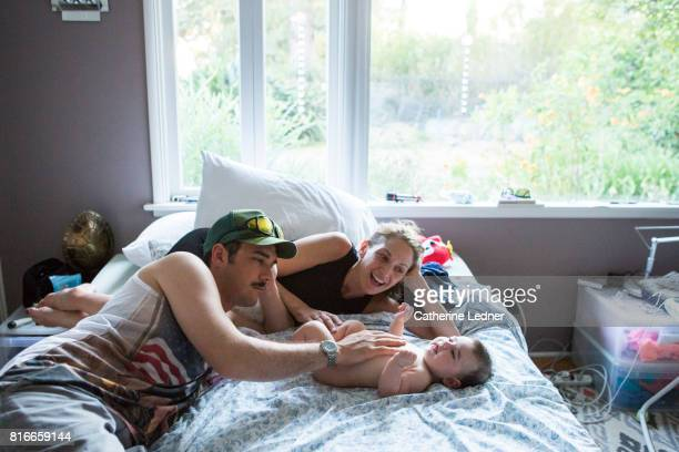 Young family resting in bed with baby