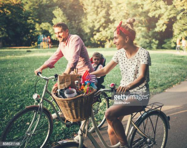young family riding bicycles in the park - bicycle stock pictures, royalty-free photos & images