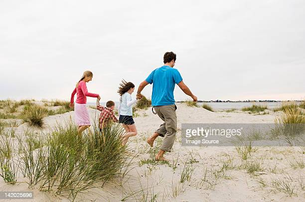 young family running on beach - chichester stock pictures, royalty-free photos & images