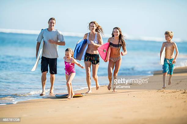 Young family running on beach with surfboards