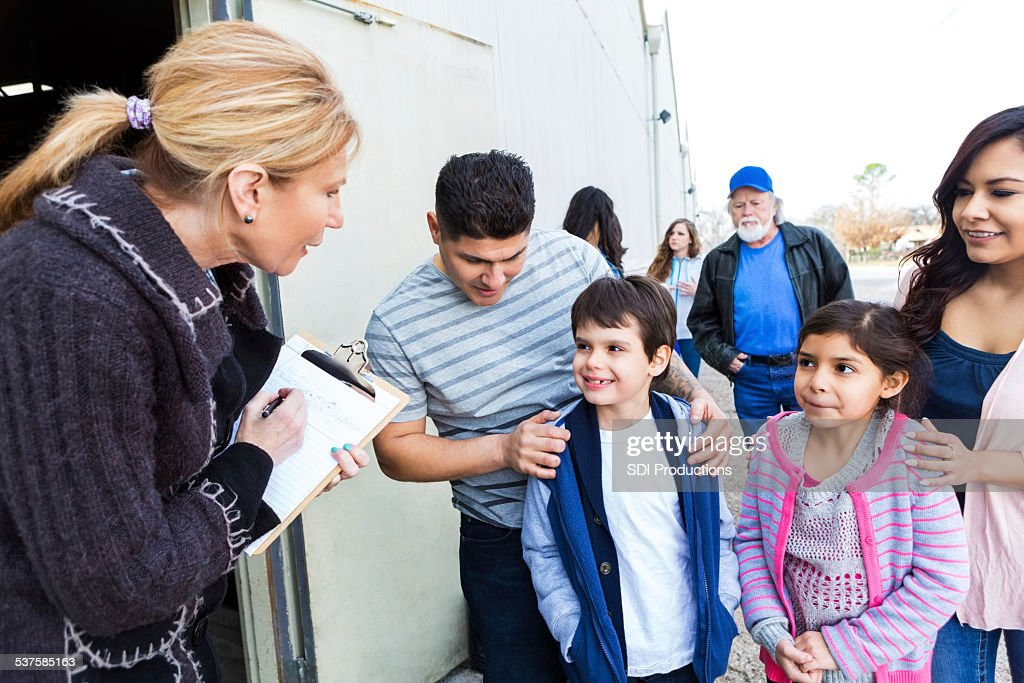 Young family signing up to volunteer at community charity : Stock Photo