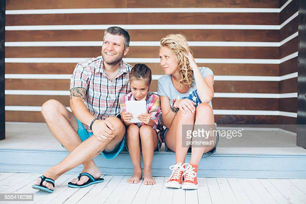 Young family sitting and using digital tablet