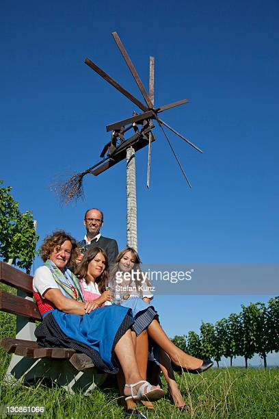 Young family sitting in front of a Klapotetz, a wind-rattle scarecrow, Southern Styria, Styria, Austria, Europe