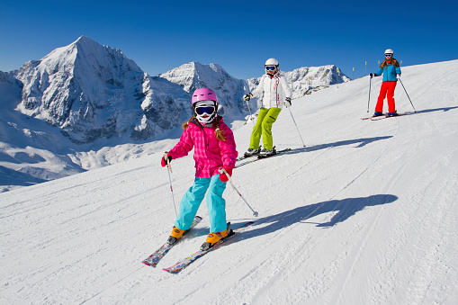 Young family skiing down a snowy slope 155344279