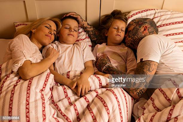 Young family sleeping together in the bedroom.