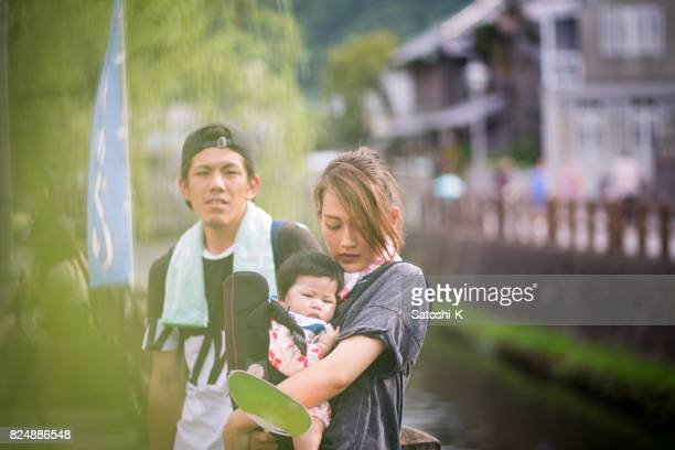 Young family standing on street in traditional Japanese town