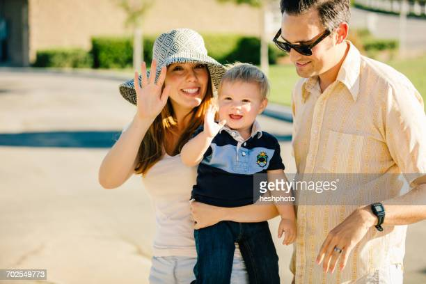young family standing together outdoors, mother and young son waving - heshphoto stock pictures, royalty-free photos & images