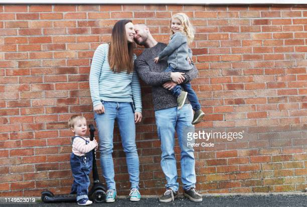 young family stood in front of red brick wall - primary age child stock pictures, royalty-free photos & images