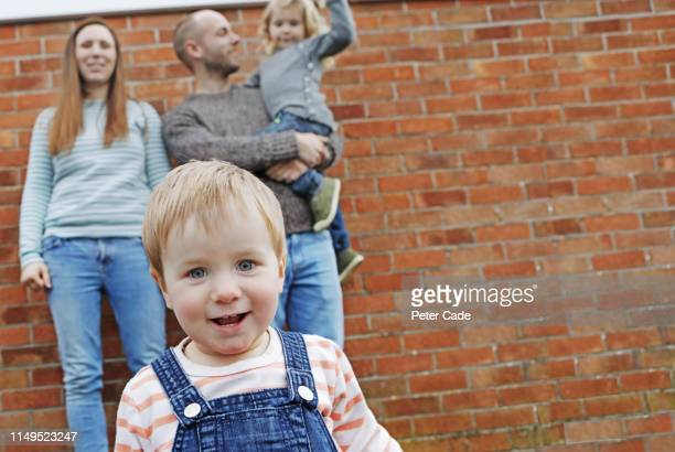 young family stood in front of red brick wall - mid adult stock pictures, royalty-free photos & images