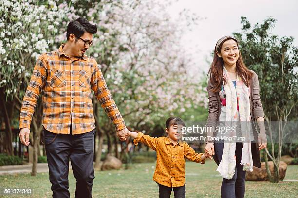 young family strolling in the lawn joyfully - femme entre deux hommes photos et images de collection